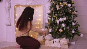 Den unga kvinnan nära spisen i jul sätter gåvor under julgranen för hans familj arkivfilmer