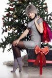 Den unga kvinnan nära träd för nytt år gör shopping Royaltyfri Bild