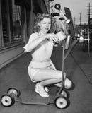 Den unga kvinnan önskar att hennes sparkcykel ska flyga (alla visade personer inte är längre uppehälle, och inget gods finns Leve Arkivbilder