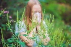 Den unga kvinnan nyser på grund av en allergi till korsörten Royaltyfri Fotografi