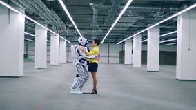 Den unga kvinnan och en cyborg kramar och talar stock video