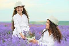 Den unga kvinnan och flickan är i lavendelfältet, härligt sommarlandskap med röda vallmoblommor Fotografering för Bildbyråer