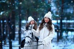 Den unga kvinnan och flickan går med miniatyrhästen i vinter parkerar arkivfoto