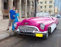 Den unga kvinnan och grabben nära den gamla amerikanska retro bilen (50th år av det sista århundradet) på den Malecon gatan Janua Royaltyfri Fotografi