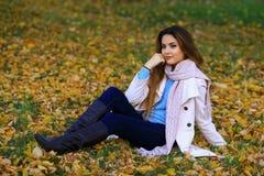 Den unga kvinnan och gul lönn för nedgång arbeta i trädgården bakgrund fritt avstånd Fotografering för Bildbyråer