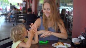 Den unga kvinnan och hennes son använder en handsanitizer i ett kafé arkivfilmer