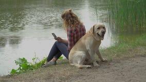 Den unga kvinnan och labrador sitter tillbaka för att dra tillbaka lager videofilmer