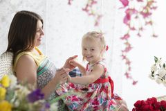 Den unga kvinnan och lilla flickan på sommaren terrasserar Royaltyfri Fotografi