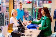 Den unga kvinnan och mannen i kläderna shoppar Arkivfoto