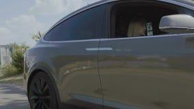 Den unga kvinnan och mannen sitter i lyxig bil och står på vägen lager videofilmer