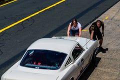 Den unga kvinnan och mannen skjuter den t?vlings- bilen royaltyfri foto