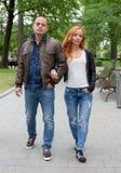 Den unga kvinnan och mannen som går i stad, parkerar Royaltyfria Bilder