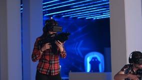 Den unga kvinnan och mannen som spelar VR-skytten, spelar med virtuell verklighetvapen och vrexponeringsglas Royaltyfri Bild