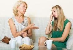 Den unga kvinnan och mognar modern som har allvarligt samtal Royaltyfria Bilder