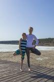 Den unga kvinnan och pojken som gör göra trädet, poserar yoga Arkivfoto
