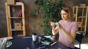 Den unga kvinnan ordnar bilder, för avhämtning kaffe, solexponeringsglas, den yrkesmässiga kameran och markören på tabellen och a stock video