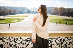 Den unga kvinnan på balkon av huset parkerar på bakgrund Royaltyfri Fotografi