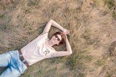 Den unga kvinnan på gräset uppskattar våren arkivfoton