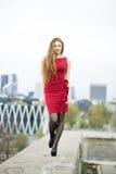 Den unga kvinnan på klänningen går på hamnplatsen Arkivbilder