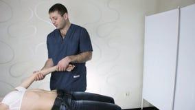 Den unga kvinnan på mottagandet på den manuella terapeuten, palpation av analysen för armbågeskarv arkivfilmer