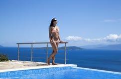 Den unga kvinnan på simbassängen tycker om solen royaltyfri fotografi