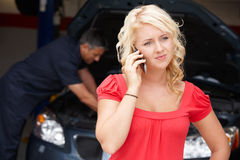 Den unga kvinnan på den auto reparationen shoppar Fotografering för Bildbyråer