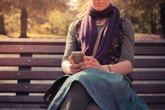 Den unga kvinnan parkerar på bänken genom att använda hennes telefon Arkivfoto
