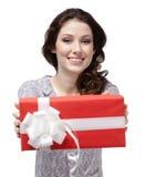 Den unga kvinnan passerar en gåva Arkivfoton