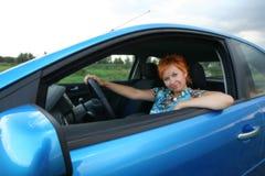 Den unga kvinnan placerar i en bil fotografering för bildbyråer