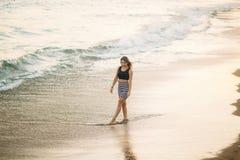 Den unga kvinnan promenerar kusten i sommartid Härlig kvinna bara arkivbilder