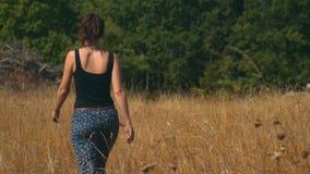 Den unga kvinnan promenerar SAD det guld- fältet i en ljus solig dag lager videofilmer