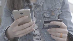 Den unga kvinnan räcker den hållande kreditkorten, när han betalar stock video