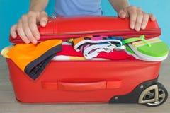 Den unga kvinnan räcker emballageresväskan Women& x27; s-kläder och tillbehör i röd resväskasaker som är förberedd för lopp Royaltyfri Foto