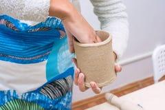 Den unga kvinnan räcker framställning av en kopp av rå lera Arkivbilder