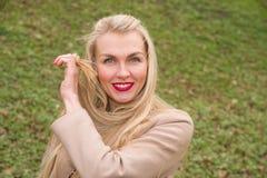 Den unga kvinnan rätar ut hennes hår i vinden Royaltyfria Bilder