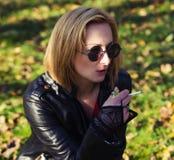 Den unga kvinnan röker på gatan arkivfoto