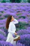 Den unga kvinnan ?r i lavendelblommaf?ltet, h?rligt sommarlandskap royaltyfri fotografi