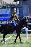 Den unga kvinnan rider en häst Arkivbild