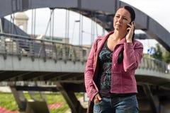 Den unga kvinnan ringer på utomhus Arkivfoton