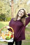 Den unga kvinnan rymmer en picknickkorg royaltyfria foton