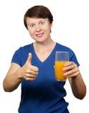 Den unga kvinnan rymmer ett exponeringsglas av orange fruktsaft 库存图片