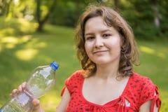 Den unga kvinnan rymmer flaskan med vatten i hand royaltyfria foton