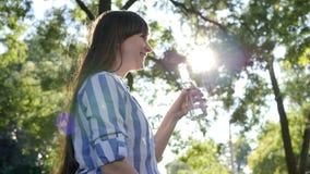 Den unga kvinnan rymmer glasflaskan i hennes hand och dricker mineralvatten på bakgrundsträd i panelljus stock video