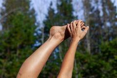 Den unga kvinnan rymmer hennes fot upp i luften, medan tycka om solen royaltyfri foto