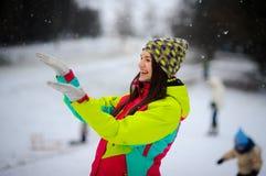 Den unga kvinnan rymmer joyfully gömma i handflatan upp under den fallande snön Arkivbild