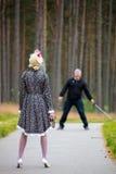 Den unga kvinnan rymmer vapnet i hand mot galningen i trät Royaltyfria Foton