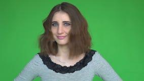 Den unga kvinnan säger inte, genom att skaka hennes huvud posera mot en löstagbar chromatangentbakgrund stock video