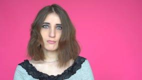 Den unga kvinnan säger ja, genom att skaka hennes huvud Posera på rosa bakgrund arkivfilmer
