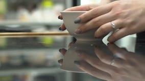 Den unga kvinnan sätter bunken på tabellen i kök av restaurangen lager videofilmer