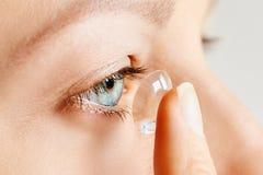 Den unga kvinnan sätter kontaktlinsen i hennes öga Eyewear, synf?rm?ga och vision, ?gonomsorg och h?lso-, oftalmologi- och optome arkivfoton